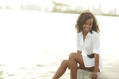 Young woman sitting by the bay Royalty Free Stock Image