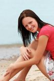 Young woman sitting on the beach Stock Photo