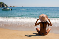 Young woman sitting on beach Stock Photography