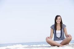 Young woman sitting on beach Stock Image