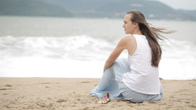 Young woman sitting on the beach with bad weather and looking on the sea. stock video footage