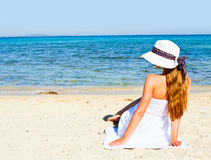 Young woman sitting on the beach Stock Photography