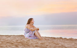 Young woman sitting on the beach at coast enjoying sea. Sunset royalty free stock image