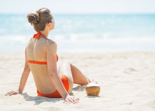 Young woman sitting on beach with coconut Stock Photography