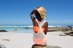 Young woman sitting on beach with a hat Royalty Free Stock Photography