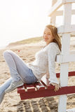 Young woman sitting on beach lifeguard chair Royalty Free Stock Photo