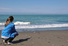 Young woman sitting on the beach looking at the sea Royalty Free Stock Photos
