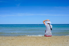 Young woman sitting on beach and looking to a sea Royalty Free Stock Photo