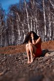 Young woman sitting on the beach in a red dress Royalty Free Stock Images