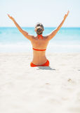 Young woman sitting on beach and rejoicing. rear view Royalty Free Stock Photo