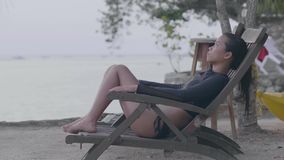 Young woman sitting on beach`s chair relaxing in the tranquil beach resort. Sitting in front of the ocean unwinding in a stock footage