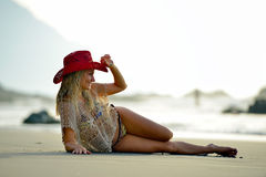 Young woman sitting on the beach in summer evening Royalty Free Stock Image