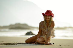 Young woman sitting on the beach in summer Stock Images