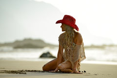 Young woman sitting on the beach in summer Stock Photo
