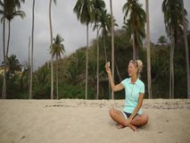 Young woman sitting on the beach and video chatting stock video footage