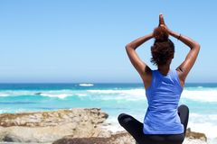 Young woman sitting at the beach in yoga pose Royalty Free Stock Images