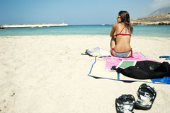 Young woman sitting on a beautiful beach Stock Image