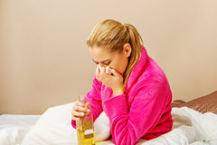 Young woman sitting on the bed crying and drinking whiskey Stock Images