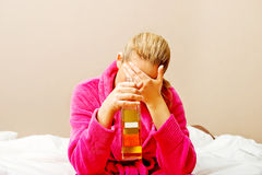Young woman sitting on the bed crying and drinking whiskey Royalty Free Stock Photo