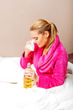 Young woman sitting on the bed crying and drinking whiskey Stock Image