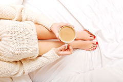 Young woman sitting in bed with a cup of coffee Royalty Free Stock Images