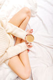 Young woman sitting in bed with a cup of coffee Stock Photography