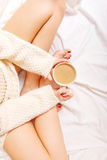 Young woman sitting in bed with a cup of coffee Stock Images