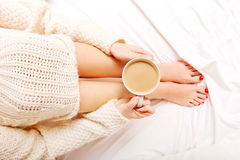 Young woman sitting in bed with a cup of coffee Royalty Free Stock Image