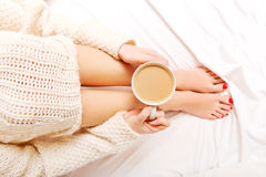 Young woman sitting in bed with a cup of coffee Royalty Free Stock Photos