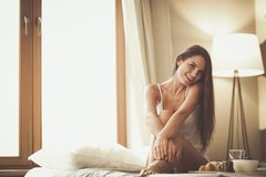 Young woman sitting in bed with a cup of milk Royalty Free Stock Photos