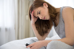 Young woman sitting on the bed Stock Image