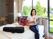 Asian woman sitting on the bed and holding flower in modern bedroom. Young woman sitting on the bed and holding flower in modern bedroom Royalty Free Stock Photo