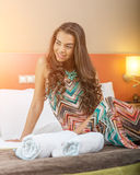 Young woman sitting in the bed of a hotel room Royalty Free Stock Photos