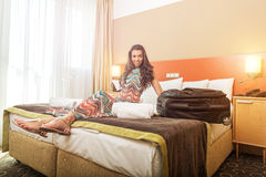 Young woman sitting in the bed of a hotel room Royalty Free Stock Images