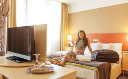 Young woman sitting in the bed of a hotel room Stock Photography