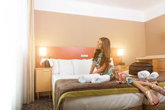 Young woman sitting in the bed of a hotel room Stock Photo
