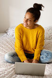 Young woman sitting on bed with laptop Stock Images