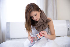 Young woman sitting on the bed with pills Stock Photo