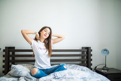 Young woman sitting in bed and strech her body at home Royalty Free Stock Photography