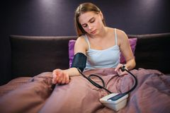Young woman sitting on bed and using blood pressure tool. She squizes small pump and looks down. Woman feels bad. royalty free stock images