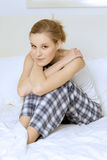 Young woman sitting in bed. Young women sitting in bed Stock Photo