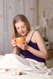Young woman sitting in bedroom and drinking coffee Royalty Free Stock Photo
