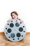 Young woman sitting behind big cinema movie reel Royalty Free Stock Photos