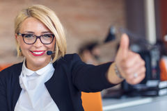Young woman sitting behind desk with thumbs up in an office Royalty Free Stock Image