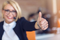 Young woman sitting behind desk with thumbs up in an office Royalty Free Stock Photo