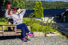Young woman is sitting on the bench and anjoying the sunny morni Royalty Free Stock Photography