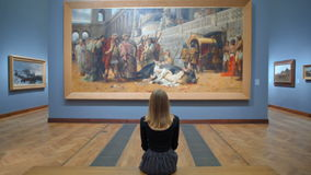 Young Woman Sitting on a Bench in the Art Gallery and Looking at a Huge Picture