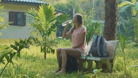 Young woman sitting on the bench at asian countryside village and drinking water. Traveler opening the plastic bottle and drinking pure water stock footage
