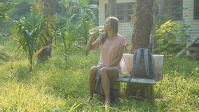 Young woman sitting on the bench at asian countryside village and drinking water. Traveler opening the plastic bottle and drinking pure water stock video footage