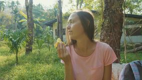 Young woman sitting on the bench at asian countryside village and eating banana. Backpacker traveler relax on trekking through local ethnic village stock footage